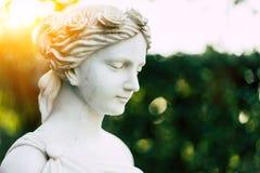 Staty av en flicka i en trädgård i solen Arkivbild