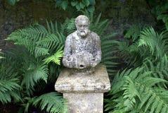 Staty av en gamal man på en sockel royaltyfria bilder