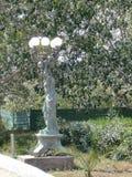Staty av en grekisk gudinna som bär enpekad lampkrans på en gata i St George - Agios Georgios Corfu, Grekland royaltyfri bild