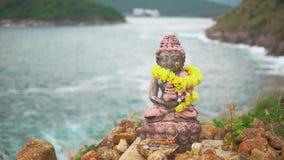 Staty av en gud med en girland av gula blommor, närbild Lugn- och harmoniatmosfär stock video