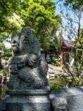 Staty av en kinesisk man på räcket av en bro Arkivfoto