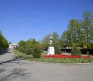 Staty av en kollektiv bonde på en sockel Legaten av den sovjetiska eran En rabatt med tulpan och barnträd in arkivbilder
