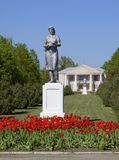 Staty av en kollektiv bonde på en sockel Legaten av den sovjetiska eran En rabatt med tulpan och barnträd in arkivfoto