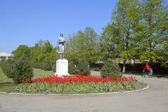 Staty av en kollektiv bonde på en sockel Legaten av den sovjetiska eran En rabatt med tulpan och barnträd in arkivfoton