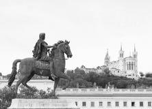 Staty av en man på hästryggen som ser domkyrkan av Fourvière i staden av Lyon royaltyfria foton