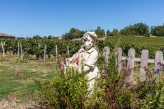 Staty av en pojke som rymmer en korg med druvor p? bakgrunden av ving?rdar i den Saint Emilion regionen france royaltyfri fotografi