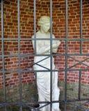 Staty av en ung flicka bak stänger på en bakgrund för tegelstenvägg Fotografering för Bildbyråer