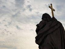 Staty av ett helgon med ett kors, himmel som en bakgrund Royaltyfria Bilder
