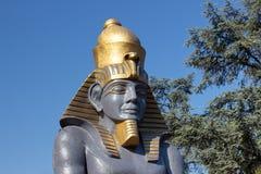 Staty av farao mot en bakgrund av blå himmel och träd Dekorativa skulpturer med egyptiska bevekelsegrunder Arkivfoto
