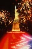 Staty av frihet med fyrverkerier och U.S.-flaggan Arkivbild