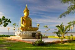 Staty av guld- Buddha på havet i Thailand Arkivfoto