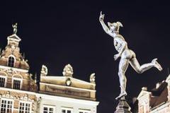 Staty av Hermes i gammal stad av Gdansk vid natt, Polen Arkivfoton