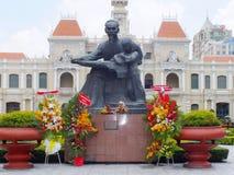 Staty av Ho Chi Minh och folks kommittébyggnad Arkivfoto