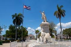 Staty av Jose Marti i den Jose Marti fyrkanten med den kubanska flaggan i Cienfuegos, Kuba royaltyfria foton
