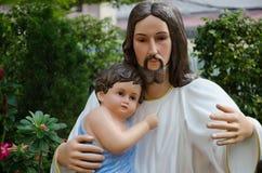 Staty av Kristus och barn i kram Arkivbild
