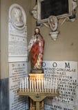 Staty av Kristus och fint sned gravstenar som dekorerar väggen på ingången till San Lorenzo i Lucina arkivfoto