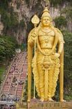 Staty av Lord Murugan med trappuppgången som leder till de Batu grottorna på bakgrunden i Kuala Lumpur, Malaysia Royaltyfria Bilder
