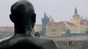 Staty av människan som ber med vikta händer och ser på den Prague sikten lager videofilmer