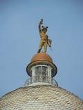 Staty av Mercury/Hermes upptill av kupolen av gammal byggnad royaltyfri bild