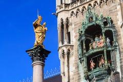 Staty av modern Mary på Munich Marienplatz mitt emot en detalj Arkivfoto