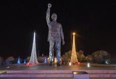 Staty av Nelson Mandela på natten som omges av julanständigheter Arkivfoto