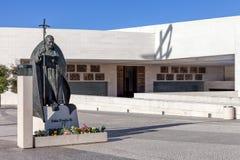 Staty av påven John Paul II med basilikan av mest helig Treenighet i bakgrund Arkivbild