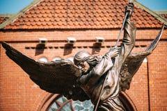 Staty av ärkeängeln Michael nära röd katolsk kyrka av St Simon And St Helena Arkivbilder
