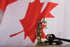 Staty av Themis och domares auktionsklubba på en bok Flagga av Kanada in Royaltyfri Fotografi