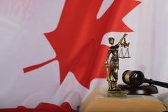 Staty av Themis och domares auktionsklubba på en bok Flagga av Kanada in Fotografering för Bildbyråer