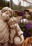 Staty av två bröder mot bakgrunden av en trevlig trädgård royaltyfri bild