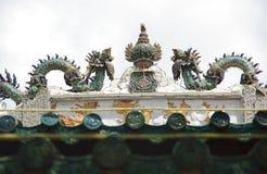 Staty av två drakar som slåss för ägg på taket av en tempel Arkivbild