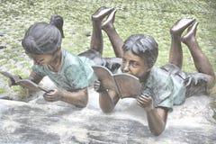 Staty av ungar som läser i Bangkok arkivbild