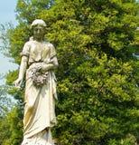 Staty för ung kvinna med blommor i en kyrkogård Royaltyfria Bilder