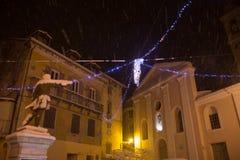 Staty in från av en kyrka i Korsika, under snöfallet royaltyfria foton