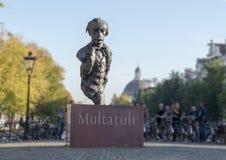 Staty Multatuli på en kanalbro i Amsterdam, Nederländerna arkivbilder