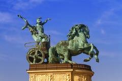 Staty som föreställer kriget, en man som rymmer en orm på en triumfvagn, på en kolonnad i hjältefyrkanten eller Hosok Tere, Budap royaltyfria bilder