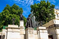 Statyer av den Elizabeth The Queen Mother och för konung George droppen som placeras i Carlton Gardens, nära gallerian i London Arkivbild