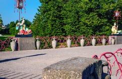 Statyer av kines med stora lyktor på poler som sitter på den stora kinesiska bron Royaltyfria Bilder