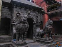 Statyer av lejon och sned portar i den historiska mitten av Katmandu arkivbild