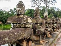 Statyer av stendivaen eller gudar i Hinduism på den främre porten av Angkor Thom, Siem Reap, Cambodja royaltyfri bild