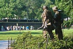 Statyer för amerikansk soldat som förbiser väggminnesmärken i Washington D C arkivfoton