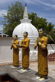 Statyer för buddistisk munk står nära en stupa på Pidurangala den buddistiska templet i Sigiriya, Sri Lanka Arkivbilder