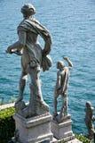 Statyer som stirrar på sjön i trädgårdarna av Isola Bella i Lago Arkivbilder