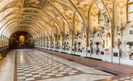 Statyer, stående och målningar i en stor korridor royaltyfria foton
