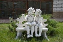 Statyett av en pojke och en flicka på en bänk royaltyfri foto