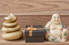 Statyett av en skratta Buddha med stenar och en stearinljus och en gåvaask, på en träbakgrund, fengshui royaltyfria bilder