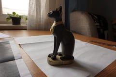 Statyett av ett svart anseende för egyptisk katt på tabellen royaltyfri foto