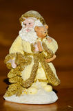 Statyett av guld- Santa Claus som lite rymmer björnen Royaltyfri Foto