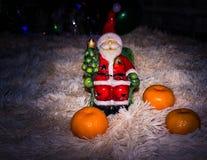 Statyett av Santa Claus med läckra och mogna apelsiner för att logarna ska skapa nytt år och jullynne Royaltyfria Bilder