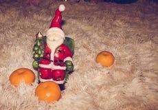 Statyett av Santa Claus med läckra och mogna apelsiner för att logarna ska skapa nytt år och jullynne Arkivfoton